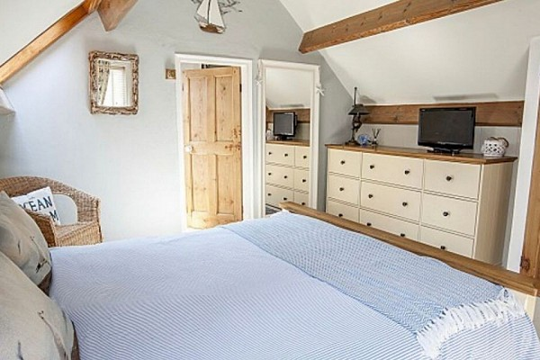 Well light bedroom, with very light blue covered bed and cream drawers