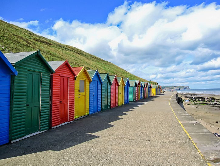 Row of colourful beach huts in Whitby, Yorkshire, England.