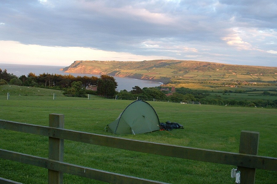 Open green space with view of the sea and a tent on the grass