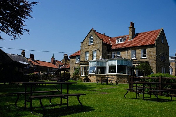 Side photo of the Fylingdales Inn, including the garden with tables and chairs, set in a blue sky background